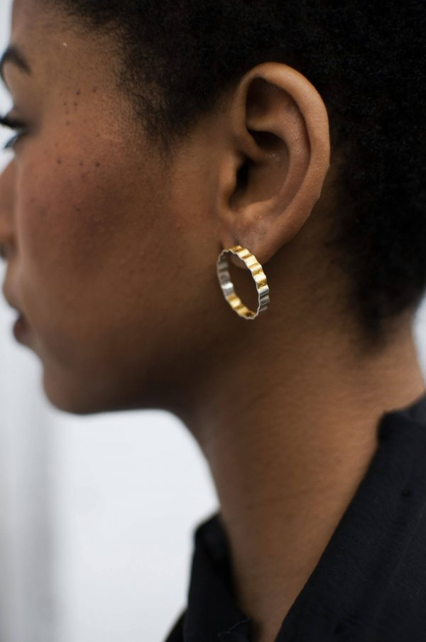 Corrugated silver earrings half covered with 24kt gold, photographed on a model