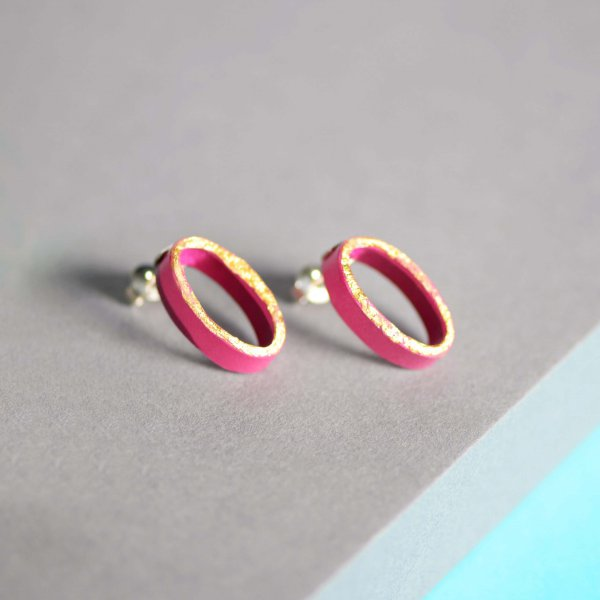 Oval earrings with gold front and painted in violet with silver studs.