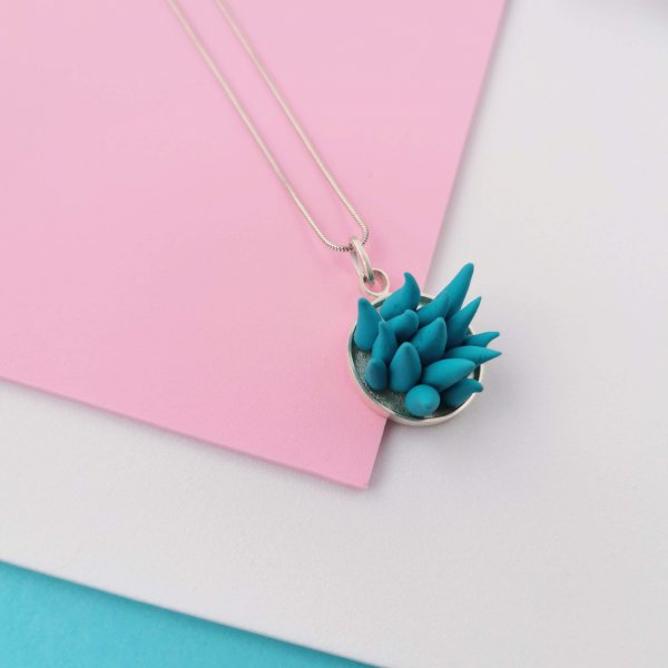 Round silver pendant with FIMO clay in teal colour ornament