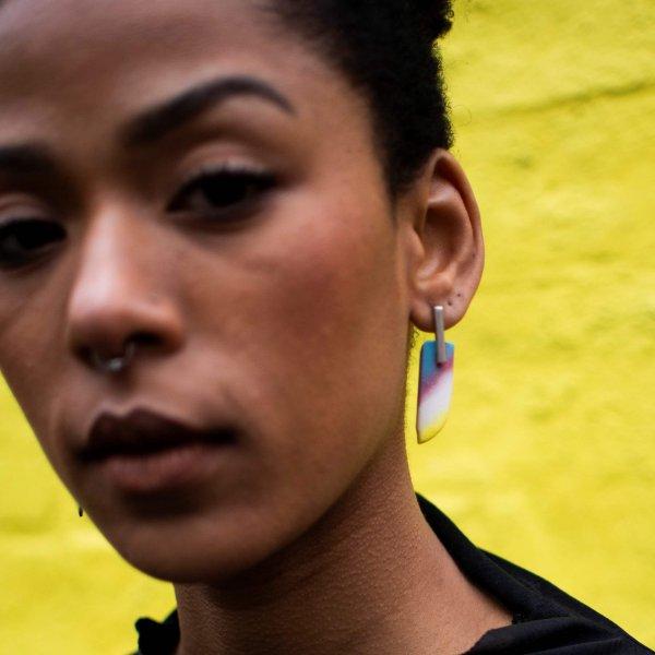 Silver stud earrings with rainbow plastic wings, handmade, on a model