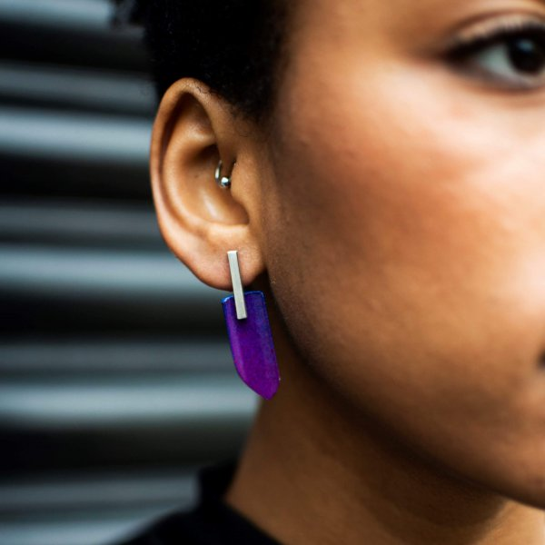 Silver stud earrings with violet and blue plastic wings, handmade, on a model