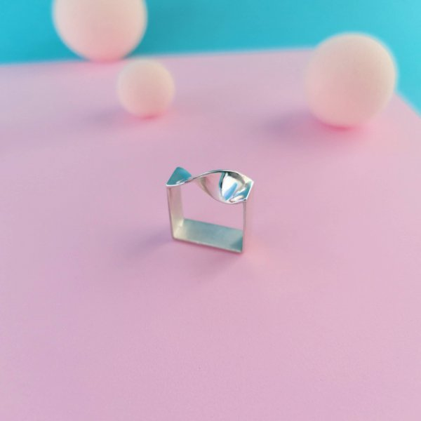 Square silver ring with twisted wave on top. Highly polished and matt finish inside.